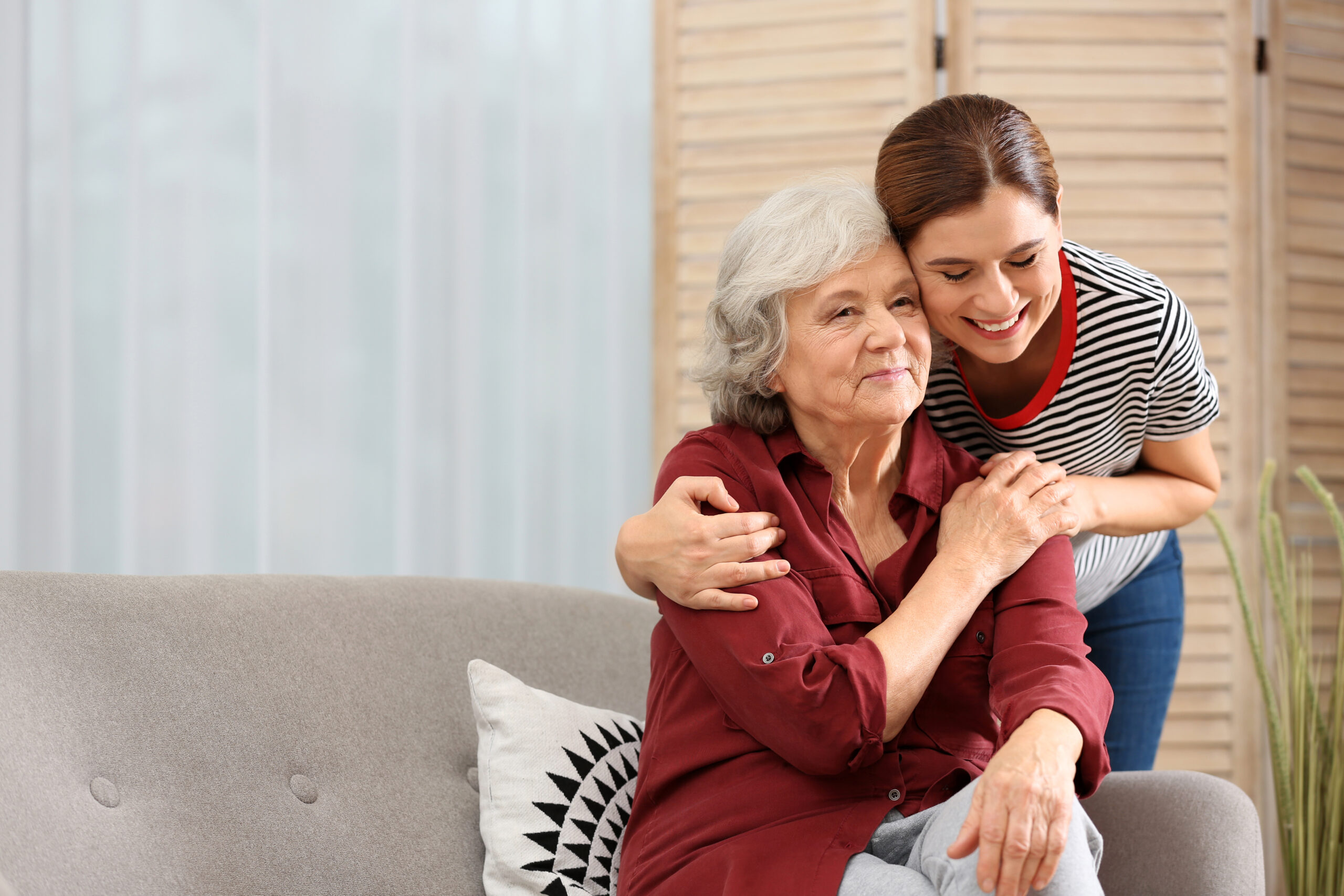 Elderly woman with female caregiver in living room. Space for text
